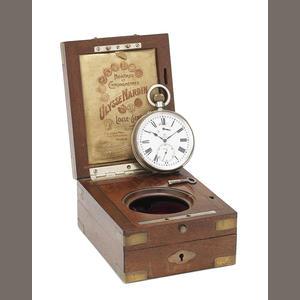 Ulysse Nardin. A silver keyless wind open face pocket watch in fixed wooden box